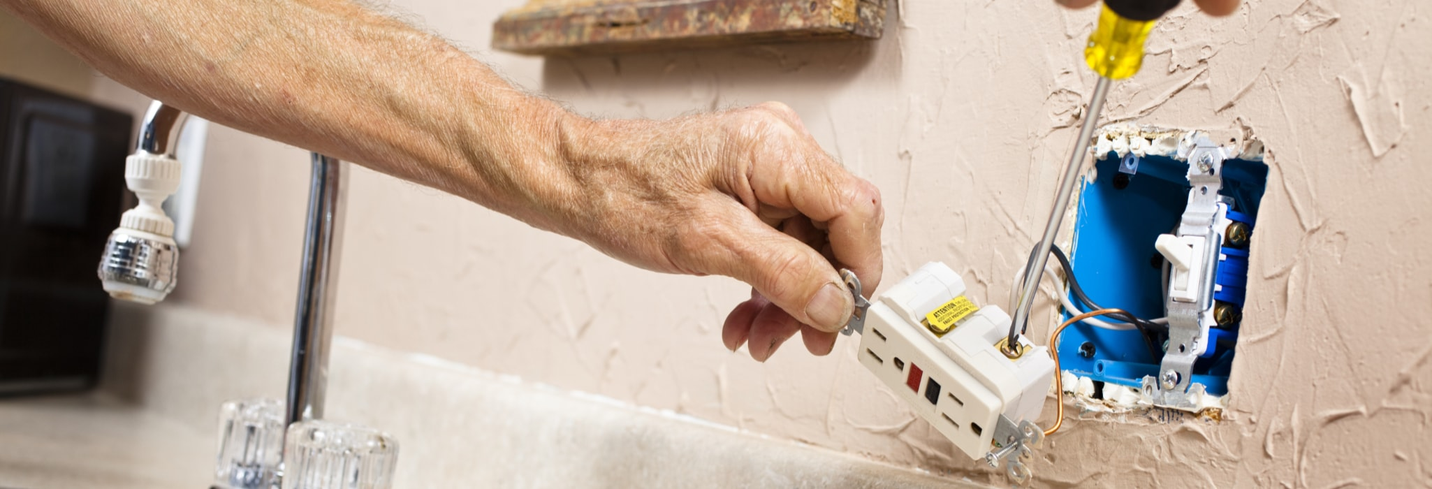 Electrician installing GFI plug in kitchen.