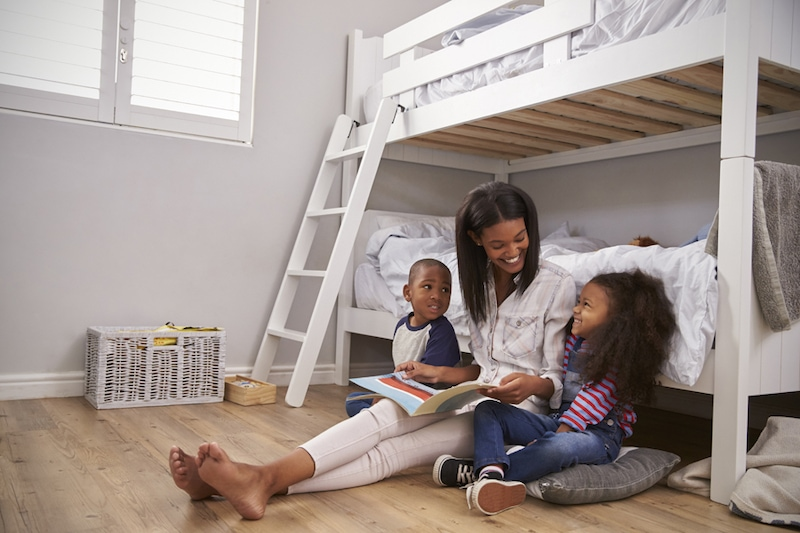 Mother Reading Story To Children In Their Bedroom