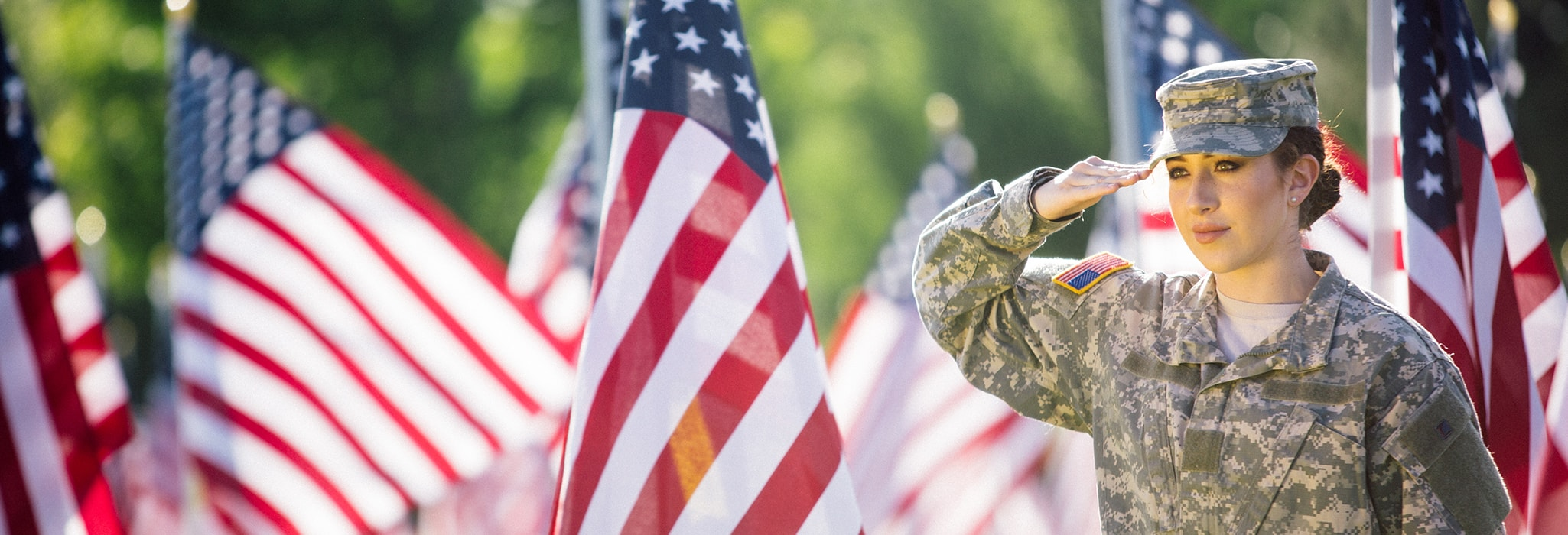 American Soldier saluting in front of flags