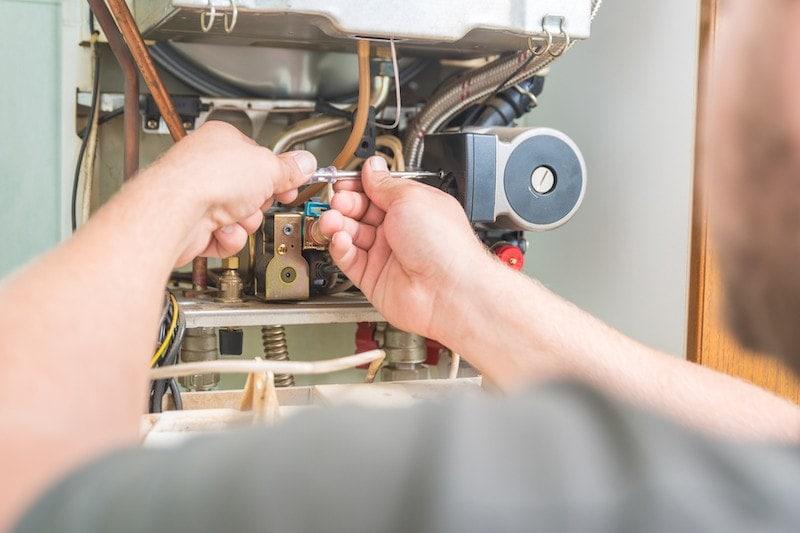 technician repairing a gas furnace